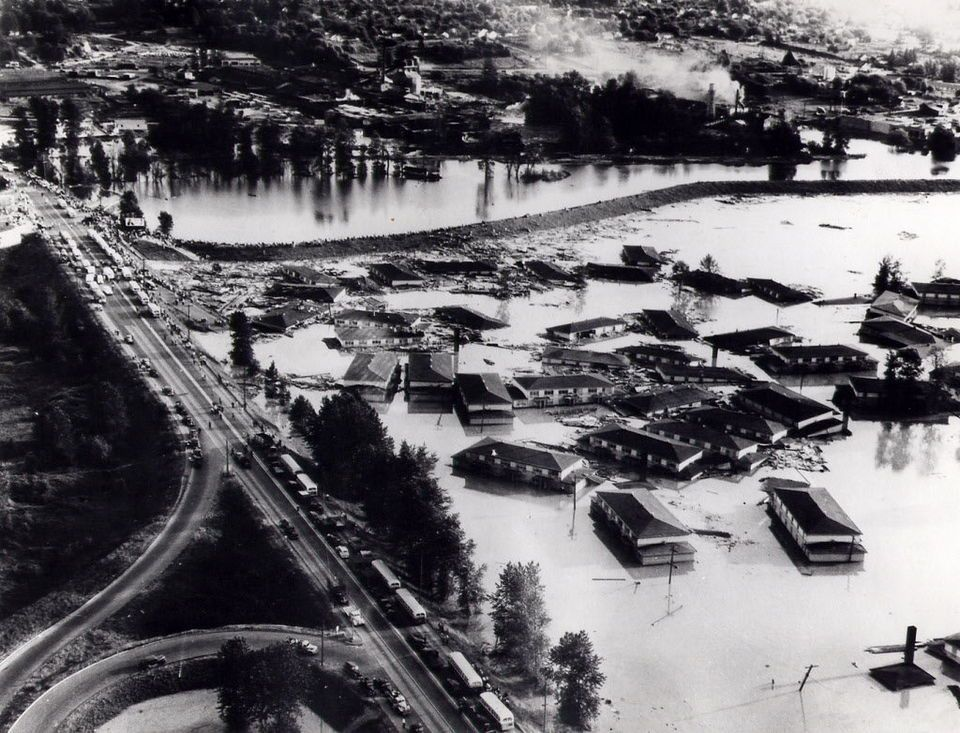 Photo of apartment buildings from Vanport wallow in floodwaters near North Denver Avenue. Buses can be seen on the road, lining up to pick up people fleeing the doomed city.