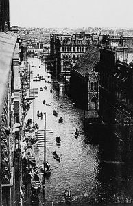 Photo of flooded downtown Portland street with people traveling via boat in June 1894