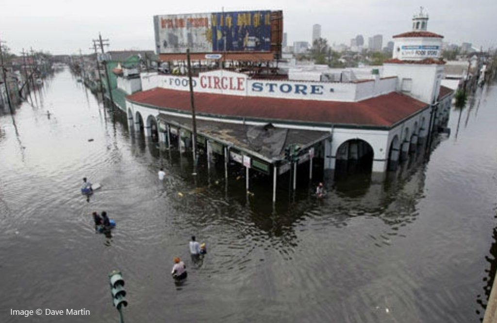 Photo of looters making their way into a grocery store on a flooded street in New Orleans in 2005