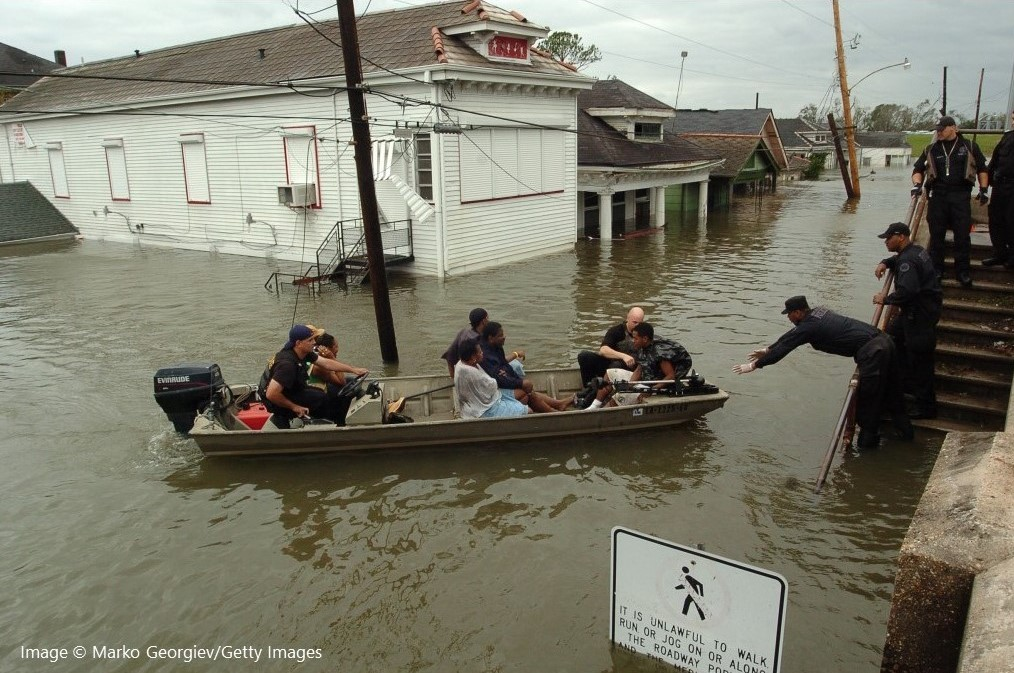 New Orleans police bring people ashore from a rescue boat in the flooded Lower Ninth Ward in New Orleans, La.