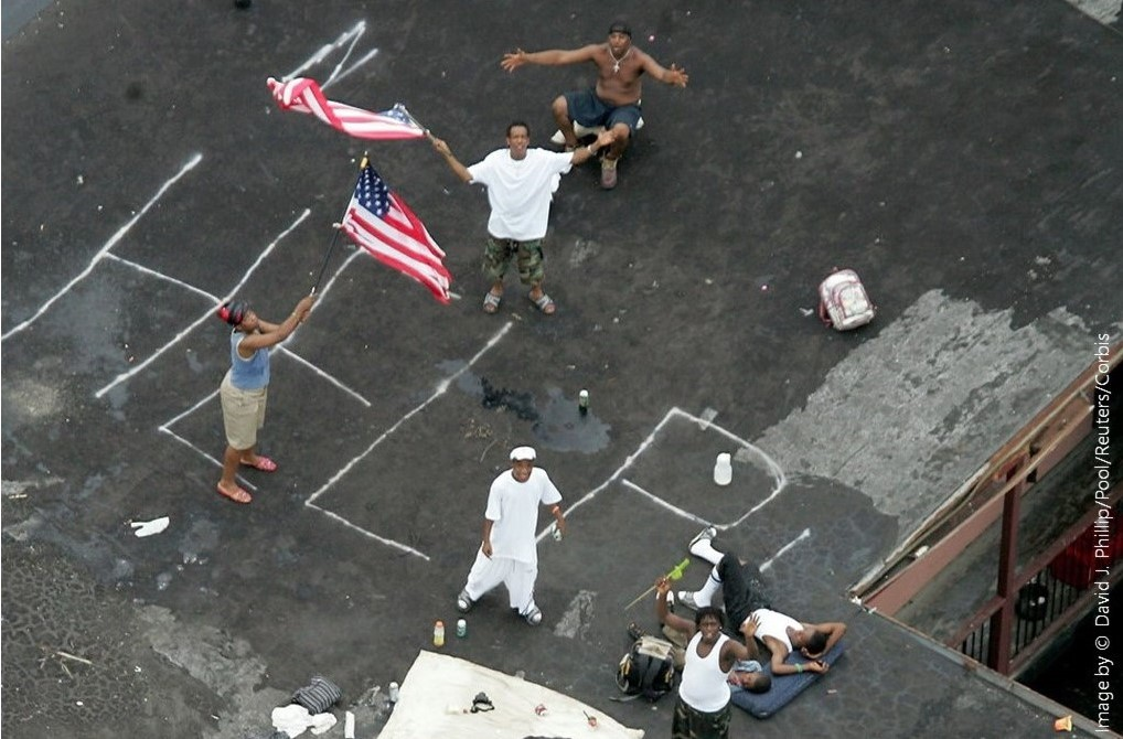Photo of New Orleans residents signaling for help from their rooftop as floodwaters rise in 2005