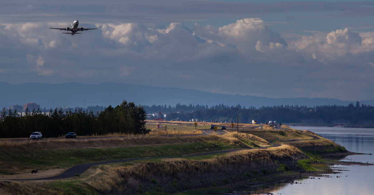 Photo of Marine Drive levee along the Columbia River with airplane taking off from the Portland International Airport behind the levee